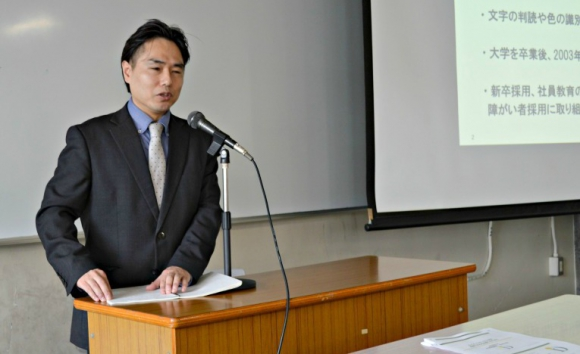 ワタミ人事部で障がい者雇用を担当する吉田良二。先天性の視覚障がいを持つ。点字ノートを使いながら講演した