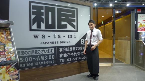 「和民」青山外苑前店の小菅店長。電気を消した店頭の看板前で