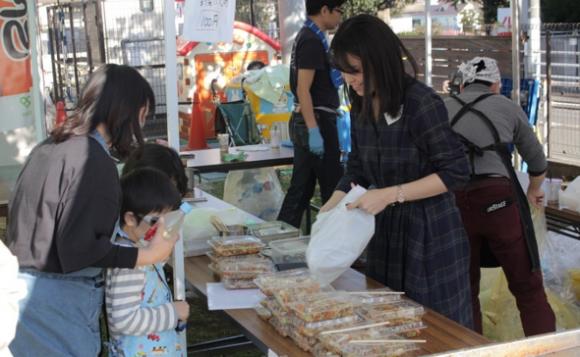 お客さんに品物を渡すワタミの江藤真見子さん(右女性)
